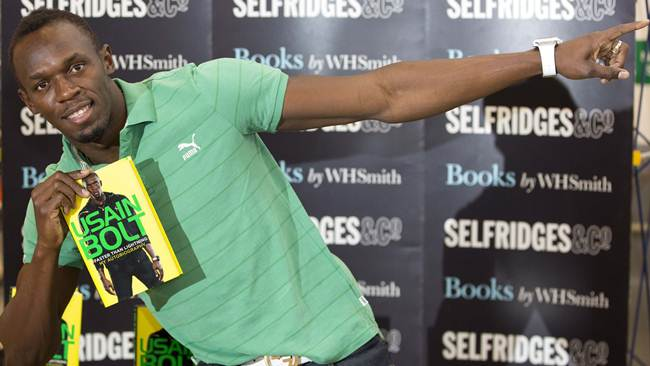 "Jamaican athlete Usain Bolt poses for photographers with a copy of his autobiography, ""Faster than Lightning,""  at Selfridges in central London"